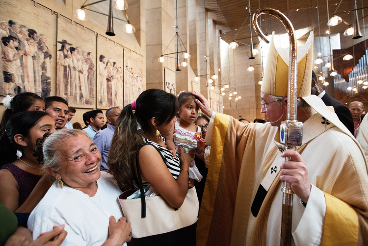 Archbishop Jose H. Gomez of Los Angeles blesses a girl during a special Mass celebrated July 17 in recognition of all immigrants at the Cathedral of Our Lady of the Angels in Los Angeles. (CNS photo/Victor Aleman, Vida Nueva)