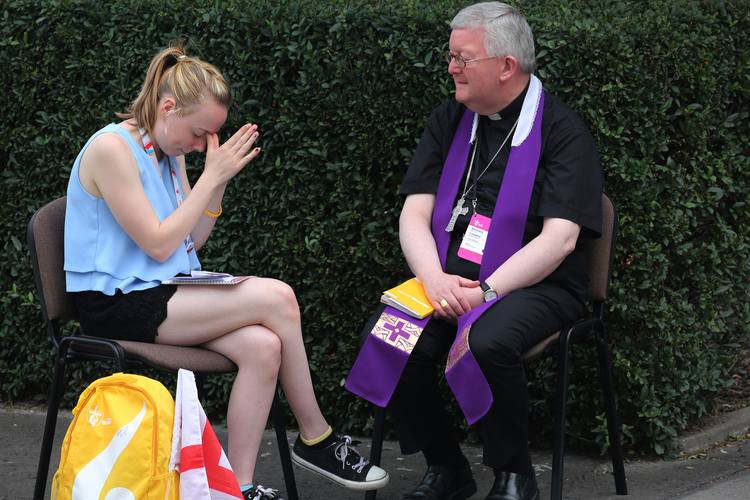 A World Youth Day pilgrim becomes emotional as a priest hears her confession at Sacred Heart Church in Krakow, Poland, July 28. (CNS photo/Bob Roller)
