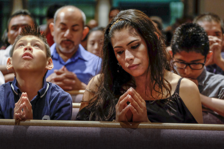 Xavier Albarran, 9, and his mother, Erika Albarran, pray during the Litany of Saints at a Mass celebrated July 27 by Bishop David R. Choby of Nashville, Tenn. (CNS photo/ Rick Musacchio, Tennessee Register)