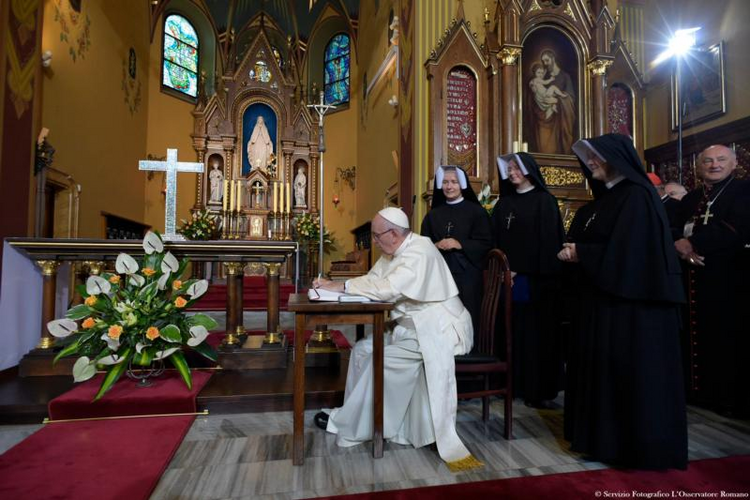 Pope Francis signs a guest book after praying at the Shrine of Divine Mercy in Lagiewniki, a suburb of Krakow, Poland, on July 30. (CNS photo/L'Osservatore Romano)