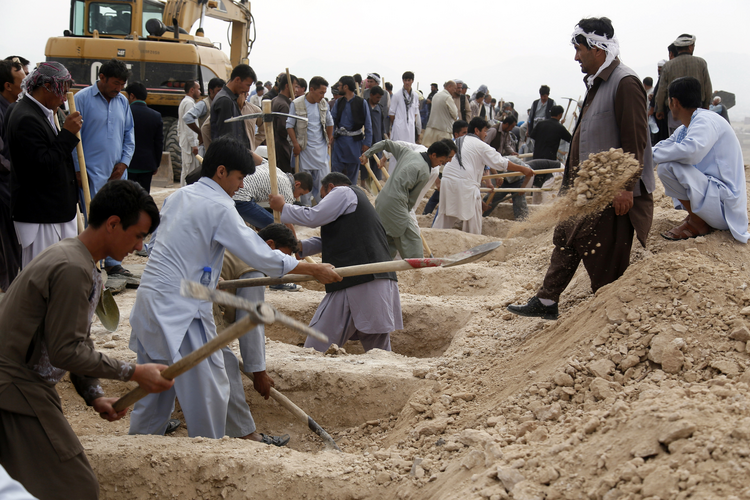 People dig graves July 24 for victims of a suicide bomb attack in Kabul, Afghanistan. The U.S. State Department's annual report on international religious freedom highlights Muslim violence against other Muslims. (CNS photo/Jawad Jalali, EPA)