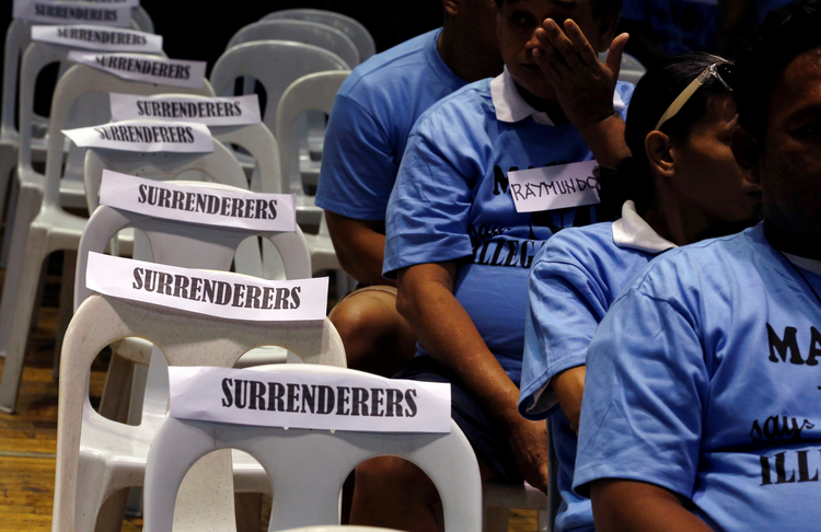 Filipino residents in Manila involved with illegal drugs wait to take a pledge that they will not use or sell narcotics after surrendering to police and government officials Aug. 18. (CNS photo/Erik De Castro, Reuters)