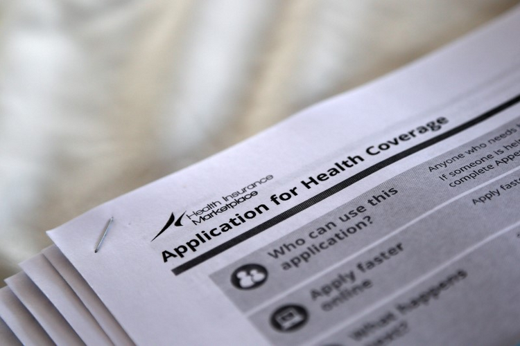 The federal government forms for applying for health coverage are seen at a 2013 rally held by supporters of the Affordable Care Act at a health care center in Jackson, Miss. (CNS photo/Jonathan Bachman, Reuters)
