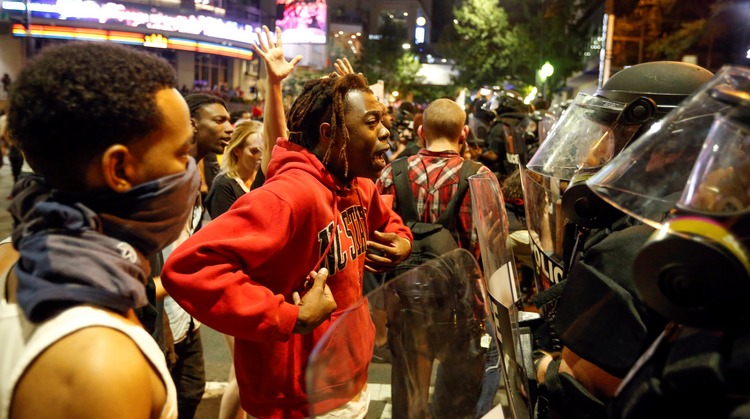 A man confronts riot police during Sept. 21 protests in Charlotte, N.C., after police fatally shot Keith Lamont Scott in the parking lot of an apartment complex. (CNS photo/Jason Miczek, Reuters)