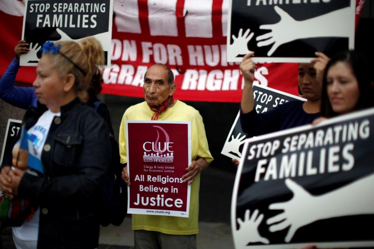 People hold signs in late May during a protest in Los Angeles against plans to deport Central American asylum seekers. Catholics and other faith leaders Sept. 28 called for action on immigration reform. (CNS photo/Lucy Nicholson, Reuters)