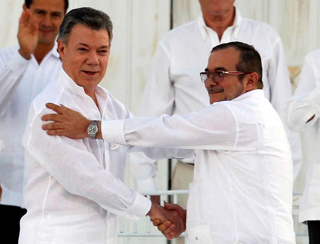 Colombian President Juan Manuel Santos and Marxist rebel leader Rodrigo Londono Echeverri of FARC, the Revolutionary Armed Forces of Colombia, shake hands Sept. 26 in Bogota. (CNS photo/John Vizcaino, Reuters)