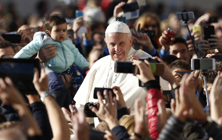 People take photos on smartphones as Pope Francis greets the crowd during his general audience in St. Peter's Square at the Vatican Oct. 12. (CNS photo/Paul Haring)