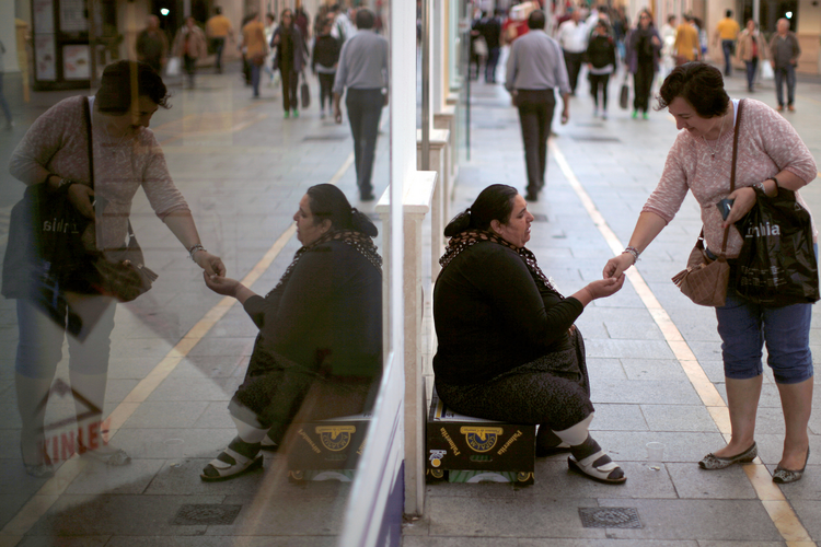 A woman gives a coin to a panhandler on Oct. 17 in Ronda, Spain. (CNS photo/Jon Nazca, Reuters)