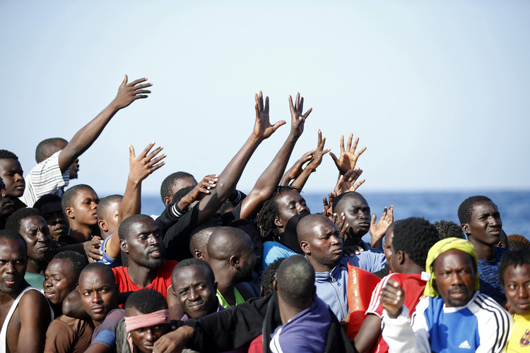 Migrants reach out from a boat during rescue operations Oct. 20 in the Mediterranean Sea. (CNS photo/Italian Red Cross via EPA)