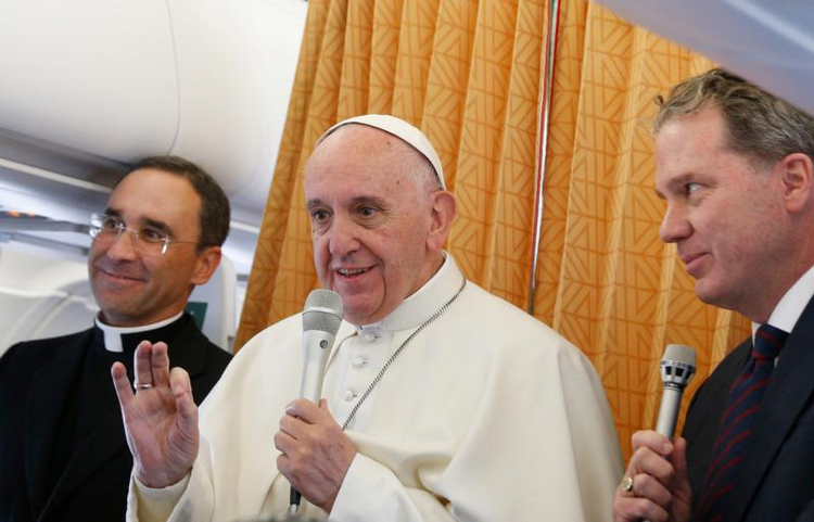 Pope Francis answers questions from journalists aboard his flight from Malmo, Sweden, to Rome Nov. 1. At left is Father Mauricio Rueda Beltz, papal trip planner; at right is Greg Burke, Vatican spokesman.(CNS photo/Paul Haring)