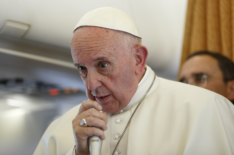 Pope Francis answers questions from journalists aboard his flight from Malmo, Sweden, to Rome Nov. 1. (CNS photo/Paul Haring)