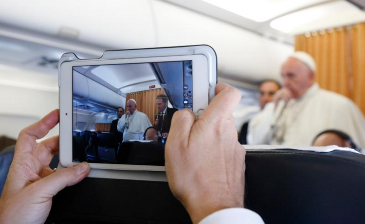 A journalist uses a tablet to photograph Pope Francis as he answers questions from journalists aboard his flight from Malmo, Sweden, to Rome Nov. 1. (CNS photo/Paul Haring)