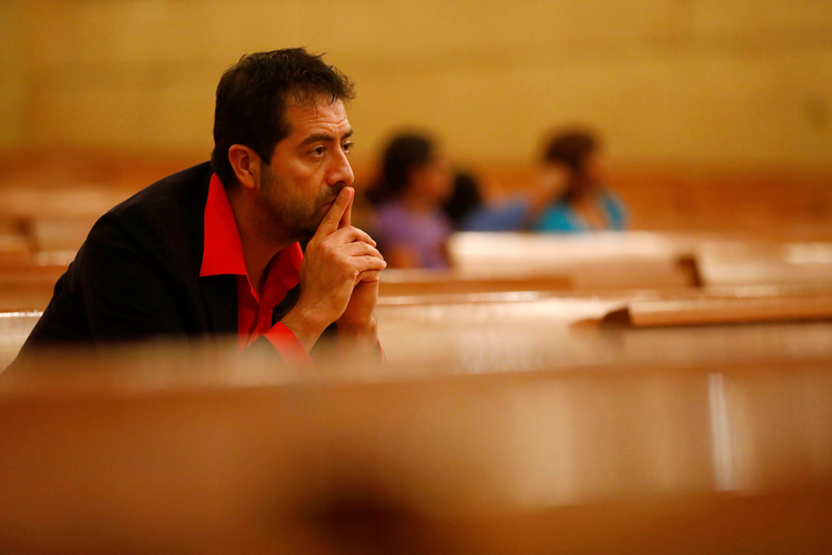 Ernesto Vega listens as Archbishop Jose H. Gomez leads an interfaith prayer service for the immigrant community in November at the Cathedral of Our Lady of the Angels in Los Angeles. (CNS photo/Patrick T. Fallon, Reuters)