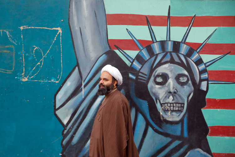 Getting Past Impressions. An Iranian cleric walks next to an anti-U.S. mural in Tehran Nov. 3. (CNS photo/Abedin Taherkenareh, EPA)
