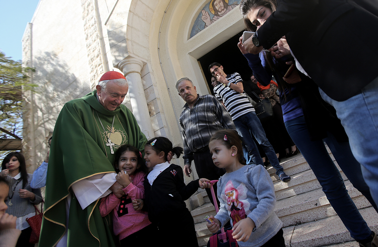 Cardinal Vincent Nichols of Westminster, England, greets children after celebrating Mass. (CNS photo/Mohammed Saber, EPA)