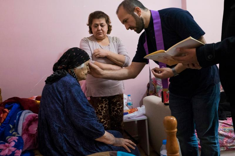 Chaldean Father Remzi Diril, also known as Father Adday, anoints Marta Kiryakos, a woman from Bartella, Iraq, who suffers from cancer, in this Nov. 10 photo. (CNS photo/Oscar Durand)