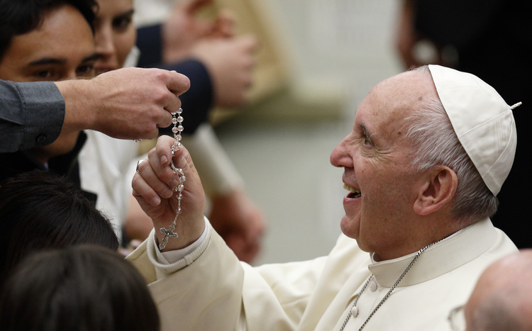 Pope Francis touches a rosary during his general audience in Paul VI hall at the Vatican Nov. 30. (CNS photo/Paul Haring)
