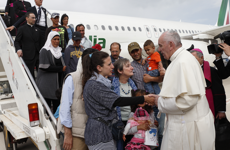 Pope Francis greets Syrian refugees he brought to Rome from the Greek island of Lesbos in April 2016 at Ciampino airport in Rome. (CNS photo/Paul Haring)