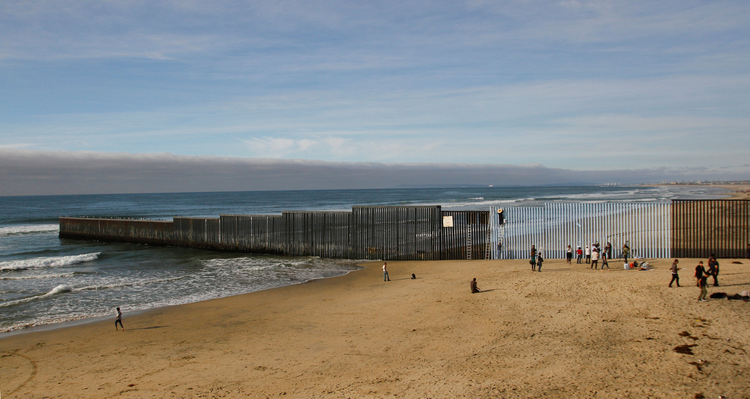 People in Tijuana, Mexico, stand next to a wall separating Mexico and the United States Dec. 10.