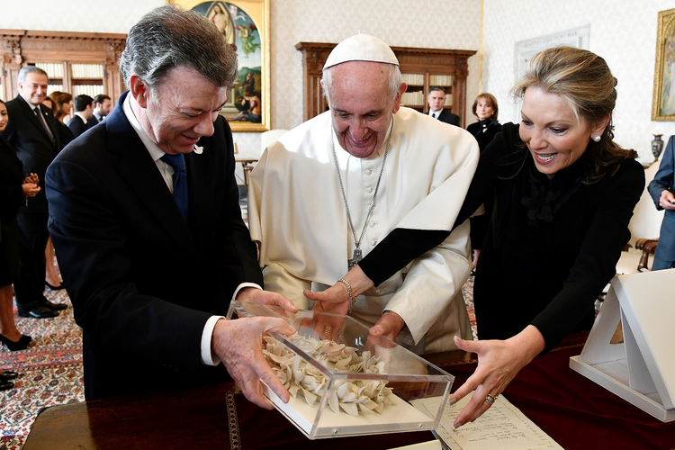 "Pope Francis receives the ""Bun of peace"" at the Vatican Dec. 16 from Colombian President Juan Manuel Santos and his wife, Maria Clemencia Rodriguez. (CNS photo/Vincenzo Pinto, pool via Reuters)"