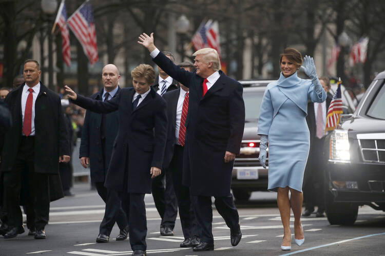 U.S. President Donald Trump and first lady Melania Trump wave as they walk with their son, Barron, along Pennsylvania Avenue during the Jan. 20 inaugural parade from the U.S. Capitol in Washington. (CNS photo/Jonathan Ernst, Reuters)