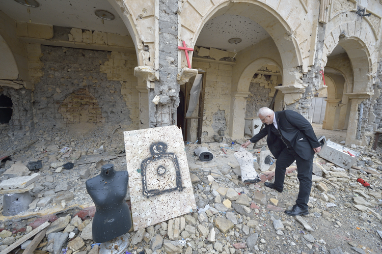 Father Emanuel Youkhana, an archimandrite of the Assyrian Church of the East, looks through the rubble of a Syriac Catholic Church on Jan. 27 in Qaraqosh, Iraq. The mannequin and poster were used as target practice. (CNS photo/Paul Jeffrey)