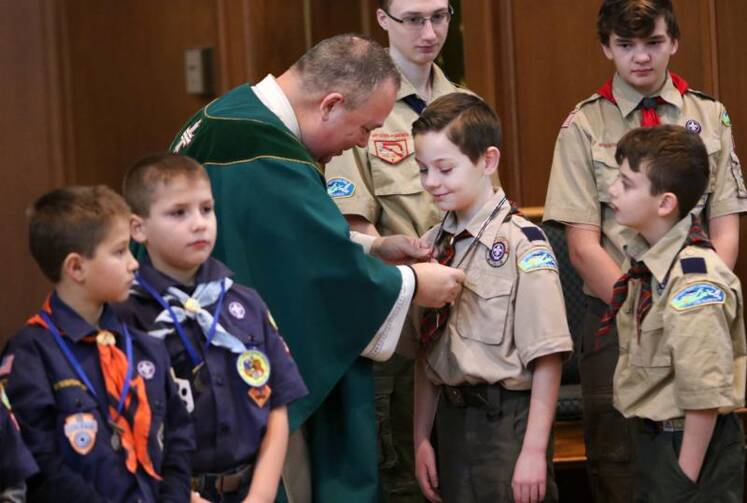Father Sean Gann presents Children of God and Light of Christ medals to Scout honorees during a Mass marking Scout Sunday at St. Joseph Church in Kings Park, N.Y., on Feb. 5. (CNS photo/Gregory A. Shemitz)