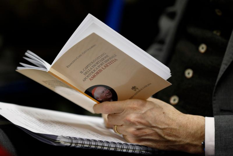 "A journalist holds a copy of a book by Cardinal Francesco Coccopalmerio, president of the Pontifical Council for Legislative Texts, on Pope Francis' apostolic exhortation, ""Amoris Laetitia,"" during its presentation at the Vatican on Feb. 14.(CNS photo/Paul Haring)"