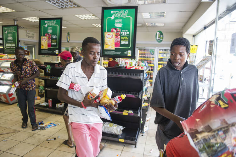 During a previous spasm of unrest related to xenophobia, protesters are seen looting a shop at a gas station in 2016 in Pretoria, South Africa. (CNS photo/Herman Verwey, EPA)