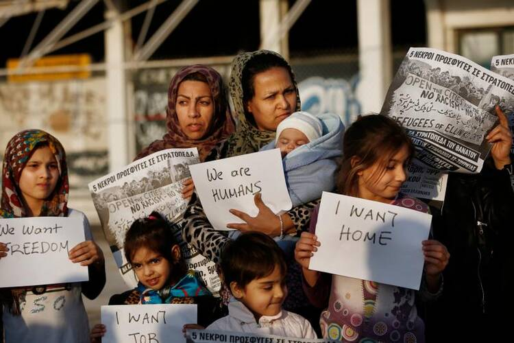 Afghan women hold placards as they take part in a protest demanding better living conditions at the refugee camp of the former international Helliniko airport in Athens, Greece, on Feb. 18. (CNS photo/Yannis Kolesidis, EPA)