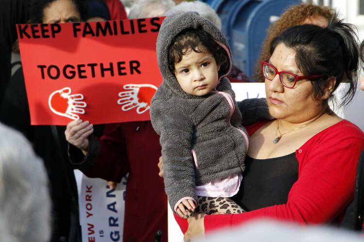 Victoria Daza, a native of Peru and an immigrants' rights activist, holds her daughter during a rally in support of immigrants in Massapequa Park, N.Y., Feb. 24. (CNS photo/Gregory A. Shemitz)