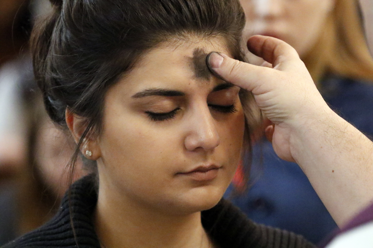 A woman receives ashes during Ash Wednesday Mass