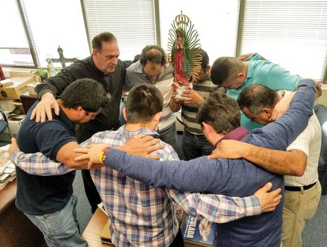 Father Jose E. Hoyos, director of the Spanish Apostolate Office of the Diocese of Arlington, Va., prays with a group of Hispanic leaders in his office on Feb. 24. (CNS photo/Mary Stachyra Lopez, Arlington Catholic Herald)