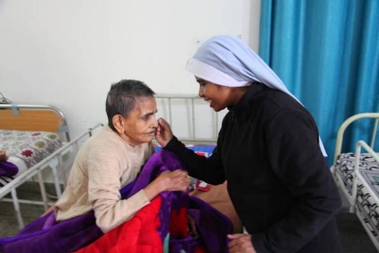 A religious sister is seen comforting a sick woman in 2016 at Snehadam Old Age Home in Gurgaon, India. Catholic Near East Welfare Association is celebrating 90 years of service to Eastern Catholic churches and the poor in the Middle East, northeast Africa, India and Eastern Europe. (CNS photo/courtesy John E. Kozar, CNEWA)