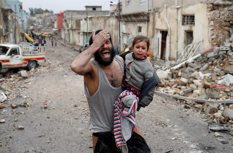 A man weeps as he carries his daughter away from an Islamic State-controlled part of Mosul toward Iraqi special forces soldiers during a battle on March 4. (CNS photo/Goran Tomasevic, Reuters)