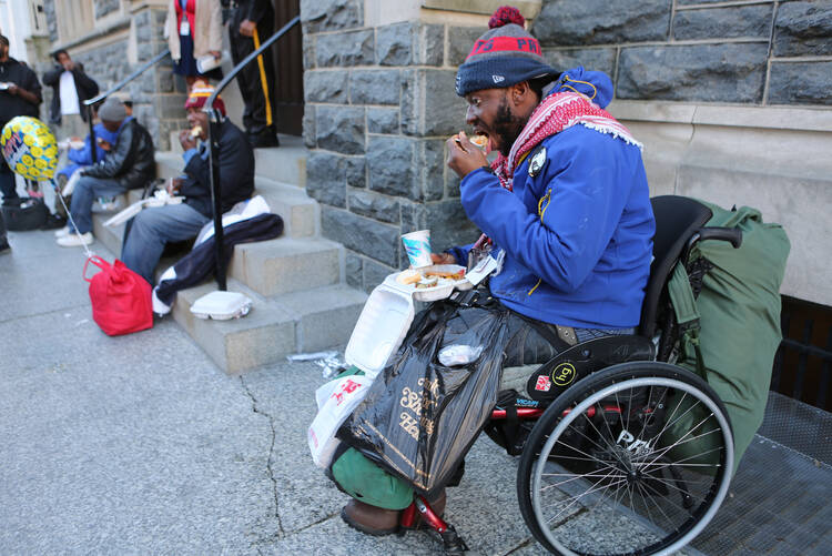 Able Putu, a homeless man in a wheelchair, eats a meal on a Washington street March 8 prepared by volunteers of the St. Maria's meals program run by Catholic Charities. Catholic Charities agencies across the United States could face huge budget holes in other areas should Congress approve the president's proposed budget. (CNS photo/Chaz Muth)