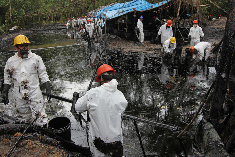 Workers collect oil from a stream below the site of an oil pipeline break in 2016 in Wachapea, Peru. Catholic leaders are calling for governments to protect the territorial rights of indigenous people suffering eviction from their lands and pollution of their water because of mining and oil operations in the Amazon basin. (CNS photo/Barbara Fraser)