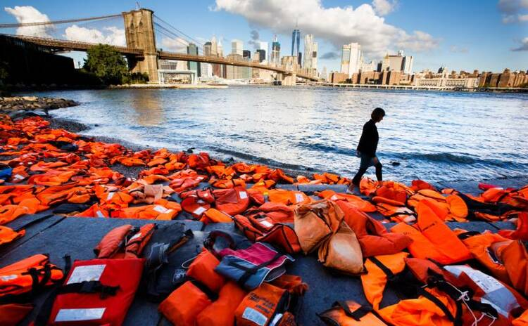 A woman in New York walks past hundreds of refugee life jackets collected from the beaches of Greece on Sept. 16, 2016. (CNS photo/Justin Lane, EPA)
