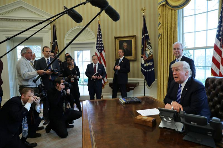 U.S. President Donald Trump talks to journalists in the Oval Office at the White House on March 24 after the American Health Care Act was pulled before a vote. (CNS photo/Carlos Barria, Reuters)