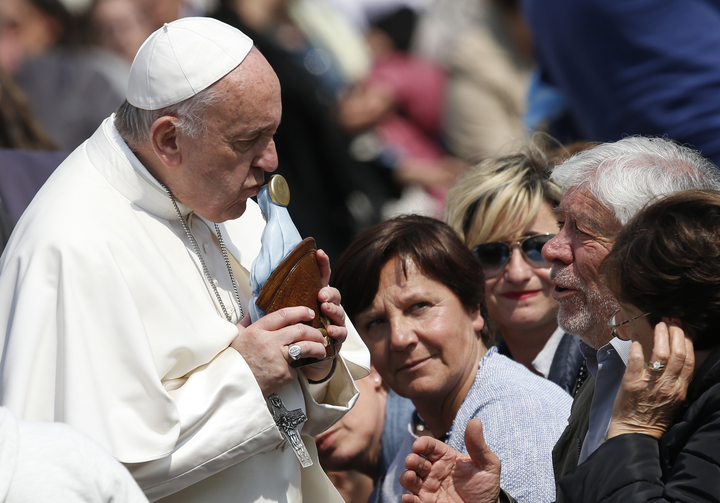 Pope Francis kisses a Marian statue presented by someone in the crowd during his general audience in St. Peter's Square at the Vatican on April 5. (CNS photo/Paul Haring)