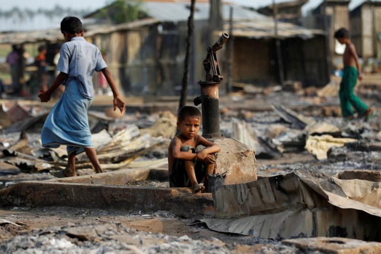 A boy sits amid debris after a 2016 fire destroyed shelters at a camp for people displaced by violence in Sittwe, Myanmar. (CNS photo/Soe Zeya Tun, EPA)