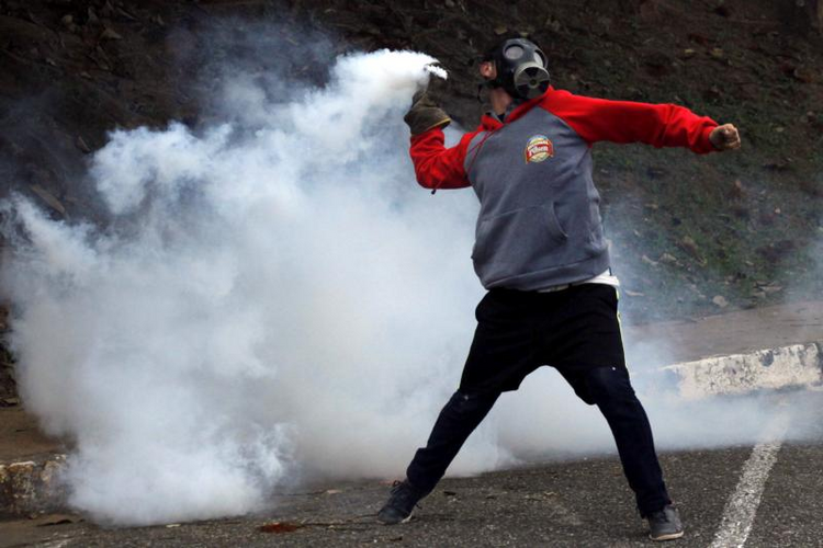 A demonstrator throws a tear gas canister back at police during an April 5 protest in San Cristobal, Venezuela. (CNS photo/Carlos Eduardo Ramirez, Reuters)
