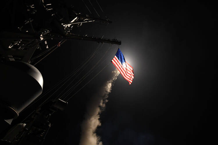 The USS Porter, in the Mediterranean Sea, fires a Tomahawk missile April 7. The U.S. Defense Department said it was a part of missile strike against Syria. (CNS photo/Ford Williams, U.S. Navy handout via Reuters)