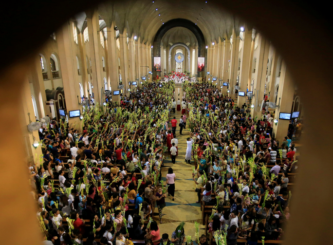 People hold palm fronds during Palm Sunday Mass on April 9 at Our Lady of Perpetual Help Church in Manila, Philippines. (CNS photo/Romeo Ranoco, Reuters)