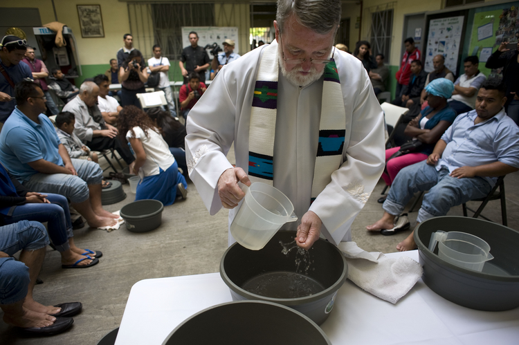 Father Pat Murphy, director of the Scalabrini-run Casa del Migrante shelter, washes his hands during a symbolic washing of feet for migrants on Holy Thursday April 13, 2017, in Tijuana, Mexico.(CNS photo/David Maung)