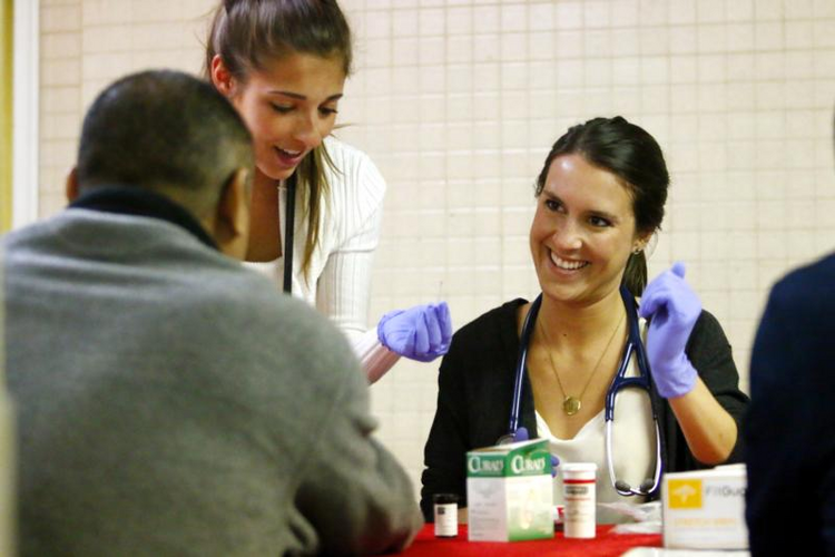 Angelica Italiano and Brighid Imperiale, first-year students at the Philadelphia College of Osteopathic Medicine, screen patients on March 5 at St. Patrick Parish's church hall in Norristown, Pa. (CNS photo/Sarah Webb, CatholicPhilly)