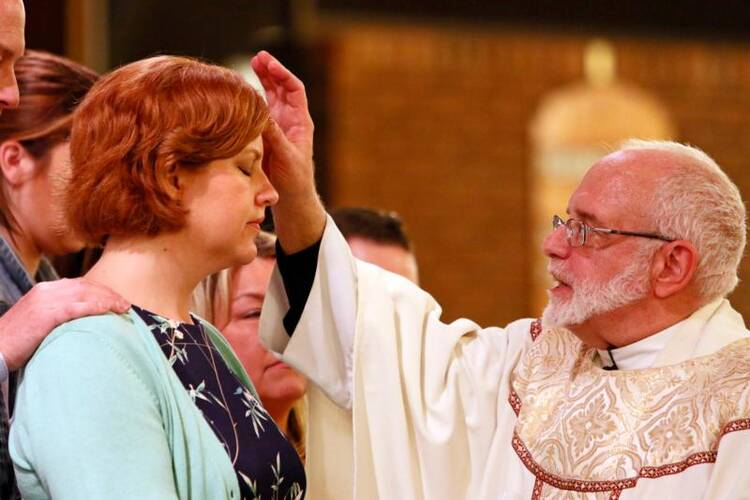 Msgr. Christopher Heller anoints Shanna Doyle with sacred chrism oil as she is confirmed during the Easter Vigil at St. Louis de Montfort Church in Sound Beach, N.Y., on April 15. (CNS photo/Gregory A. Shemitz)