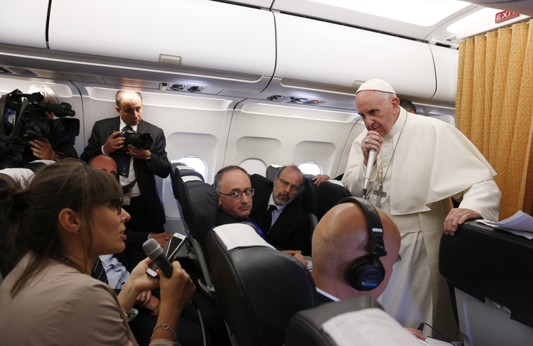 Pope Francis listens to a question from Vera Shcherbakova of the Itar-Tass news agency while talking with journalists aboard his flight from Cairo to Rome April 29. (CNS photo/Paul Haring)