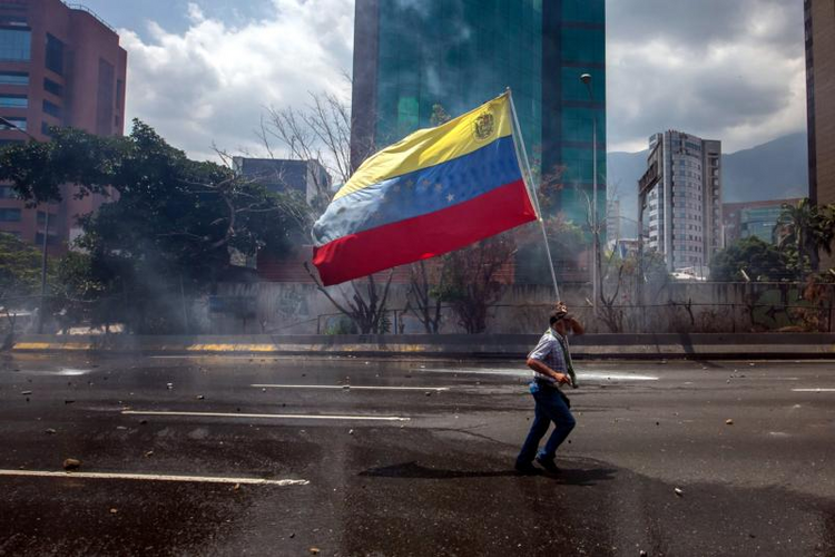 A demonstrator carries VenezuelaÕs flag in Caracas, Venezuela, on April 26. (CNS photo/Miguel Gutierrez, EPA)