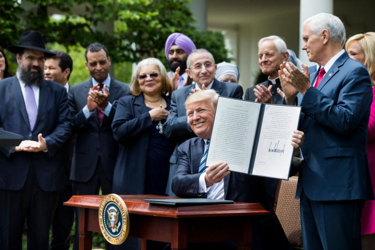 President Donald Trump shows his signed Executive Order on Promoting Free Speech and Religious Liberty during a National Day of Prayer event at the White House in Washington on May 4. (CNS photo/Jim Lo Scalzo, EPA)